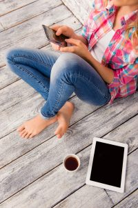 Top view photo of woman holding smartphone and typing sms