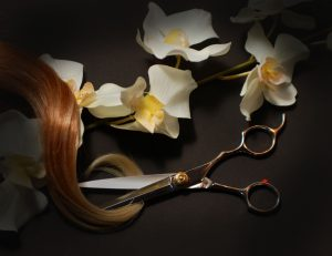 Barbering shears with blonde locks laying over a branch of white flowers