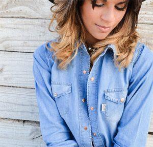 Model in denim shirt leans against a barn