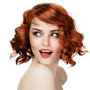 Woman with red hair and green eyes looks over her shoulder