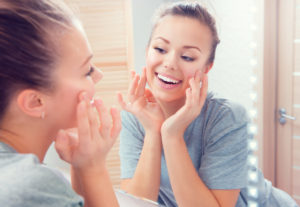 woman feeling soft skin on face